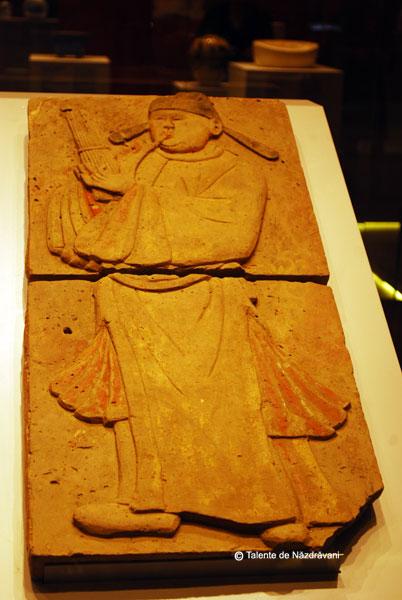 """Barbat care canta la sheng - instrument antic de tipul unui cimpoi din trestie. Perioada celor \""""Cinci dinastii si zece regate\"""", 907-960. Este unul din cei 28 de muzicieni cantand, parte a unui basorelief pictat ce decora un mormant din dinastia Tang."""
